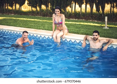 Two young men in water swimming and resting and girl in bikini sitting on edge of poolside.