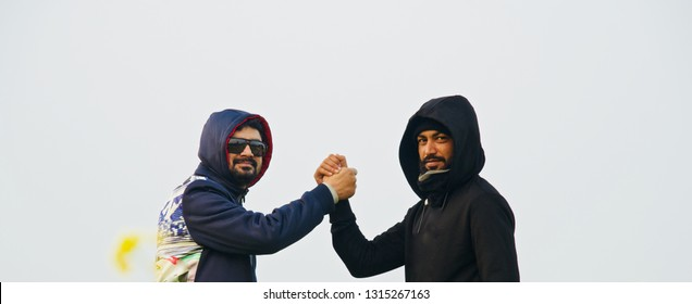 Two young men wearing hood dress holding their hands together