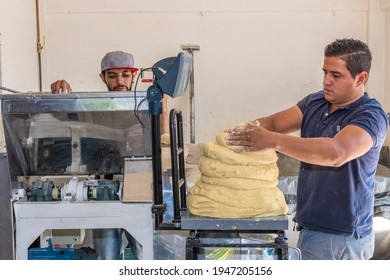 two young men working as a team to extract dough from a nixtamal mill