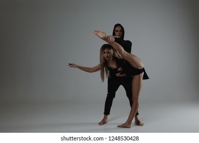 Two young modern ballet dancers posing over gray studio background