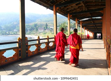 Two young monks walking on  PUNA MOCCHU BAZAM : Antique  wooden bridge at Punakha Dzong Monastery or Pungthang Dewachen Phodrang  Bhutan