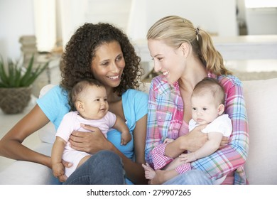 Two Young Mothers On Sofa At Home
