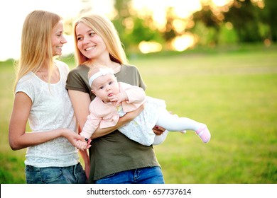 Two young mothers are walking in the park in summer with her baby. LGBT Lesbian Couple. The concept of  family and healthy lifestyle