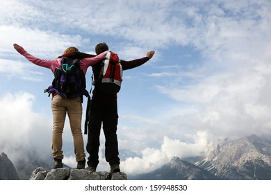 Two young mountaineers standing on mountain top and enjoying their success