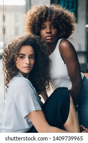 two young multiethnic and curly women posing together looking camera– youth, new generation, imaginative