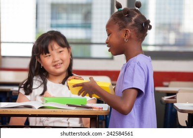 Two young multiracial african asian girls smiling at classroom desk.