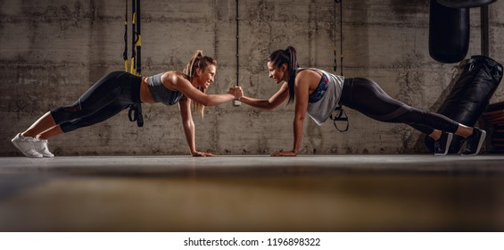 Two young muscular girls doing plank exercise at the gym workout.