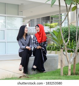 Two young muslim girl happy chatting together