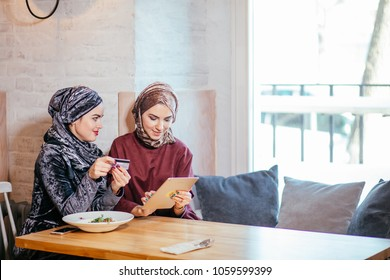 Two young Muslim women in cafe, shop online using electronic tablet