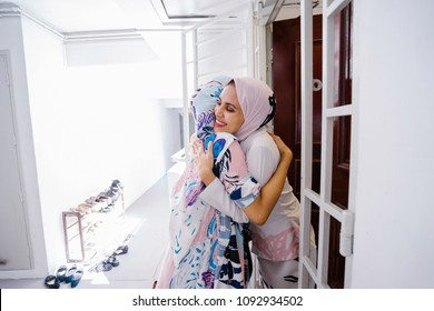 Two young Muslim women embrace as one welcomes her into her home to celebrate Hari Raya together.