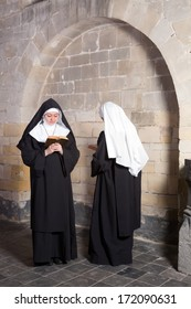 Two young nuns passing each other in a medieval convent (this is a composite, only 1 model release needed) - Shutterstock ID 172090631