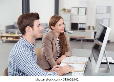 Two Young Office People Looking at the Computer Screen Together On Top of the Desk.