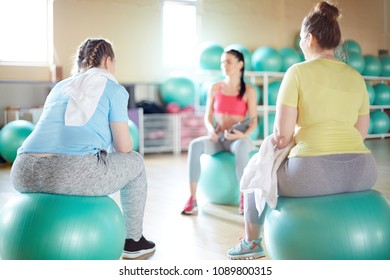 Two young oversized women in activewear sitting on fitballs in front of their fitness instructor