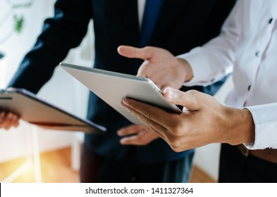 two young partner business man investor talking and reading information about financial statistics in mobile tablet together standing in office, finance, investment and digital technology concept
