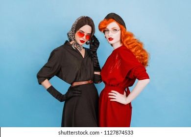 Two young passion lesbians girls with curly long hair in black dress on blue background. A beautiful retro woman with pale skin and red lips. Lesbian couple in a studio. Passion between girlfriends