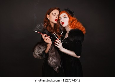 Two young passion lesbians girls with curly long hair in black dress on dark background. A beautiful retro woman with mouthpiece smoking. Lesbian couple in a studio. Passion between girlfriends