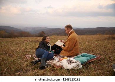 two young people, 20-29 years old, couple or friends, sitting on mountain field outdoors picnic, sitting on blanket, relaxing, man reading a book, woman listening.