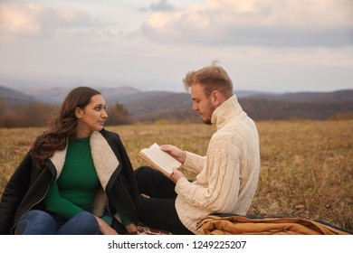 two young people, 20-29 years old, couple or friends, sitting on mountain field outdoors, relaxing, man reading a book, woman listening.