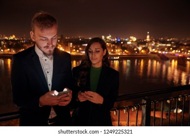 two young people, 20-29 years old, using texting smart-phones. upper body shot. night time, dark, city scape behind in background (blurry, out of focus).