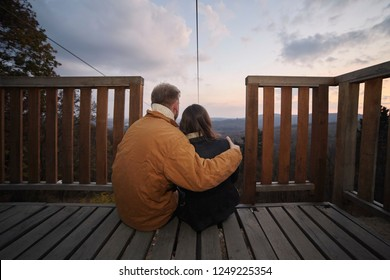 "two young people backs outdoors, sitting in front of beautiful landscape sky and clouds scenery hugging in Autumn clothing, rear view. Location is national park ""Fruska Gora"", Serbia."