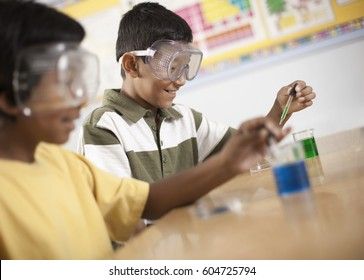 Two young people, boy and girl in a science lesson, wearing eye protectors and working on an experiment,