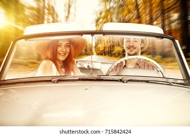 two young people in cabriolet and golden autumn road