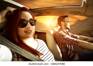 Two young people in car and autumn trip. Free space for your decoration and sunset time.
