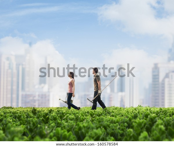 Two young people carrying gardening equipment walking across green field with plants