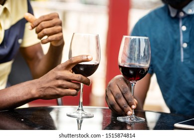 two young people celebrate a party each holding a glass of red wine