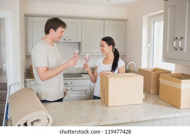 Two young people celebrating move into new home with champagne in kitchen