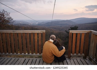 "two young people couple, hugging together, sitting on deck, looking at beautiful scenery with landscape mountains and sunset sky outdoors, in national park ""Fruska Gora"", Serbia."