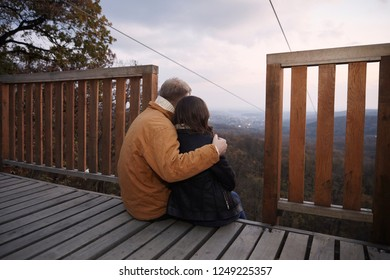 "two young people couple, hugging together while sitting on deck, looking at beautiful scenery landscape mountains with sky and beautiful clouds at dawn, outdoors. National park ""Fruska Gora"" Serbia."