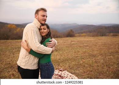 two young people, couple hugging outdoors in mountains field, on a picnic vacation.