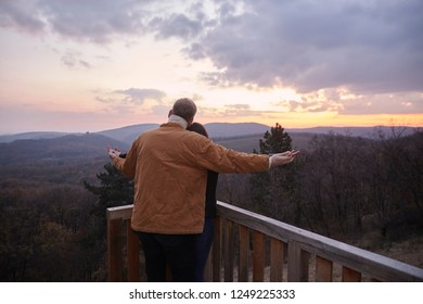 "two young people couple, man standing behind woman, holding hands together. rear view, back. Like in a popular movie, on a viewpoint looking at national park ""Fruska Gora"", Serbia."