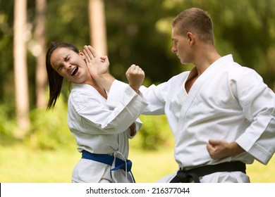 Two young people doing karate in nature.