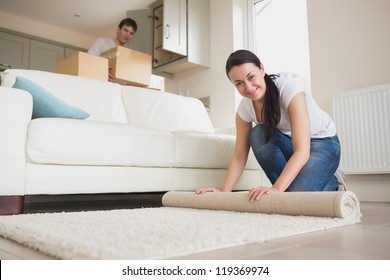 Two young people furnishing the living room of new home