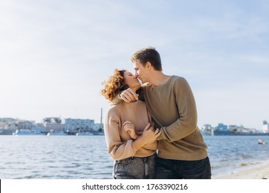 two young people in love running on the beach. They smile at each other. Holding hands. The guy kisses the girl Beautiful couple. Beach. Feeling. Dress in a sweater