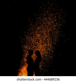 Two young people in love standing in front of fire and holding together