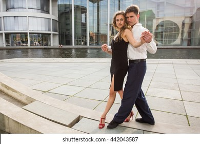 two young people - a man in white shirt and a woman wearing black dress - dancing tango outside on city embankment