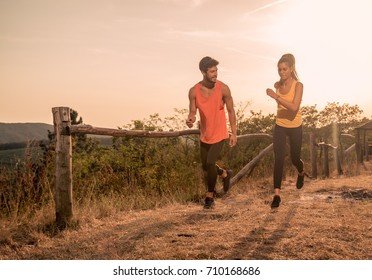 two young people, man woman, running outdoors, nature, hot summer day, warm colors, sport clothes