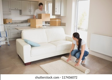 Two young people moving into their house and furnishing the living room