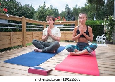 Two young people practicing yoga together on wooden patio outdoors enjoying serenity and relaxation. Couple with digital tablet participating at online yoga class