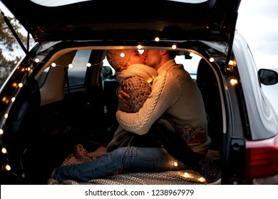 two young people in relationship hugging in the car