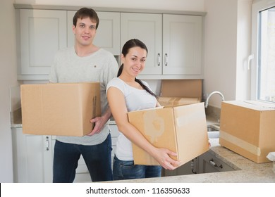 Two young people relocating in kitchen
