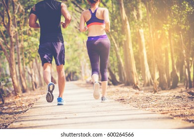 two young people running together on road. Man and woman jogging outdoors.