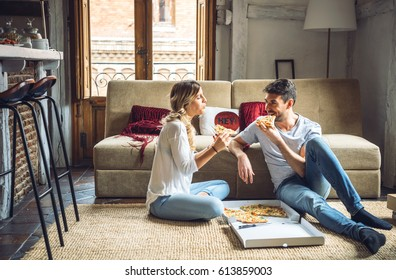 Two young people sitting on floor and sharing ordered pizza.
