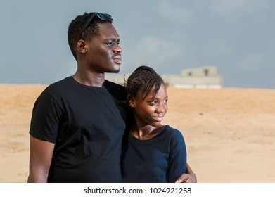 two young people standing at the beach in a black tee shirt looking straight ahead.