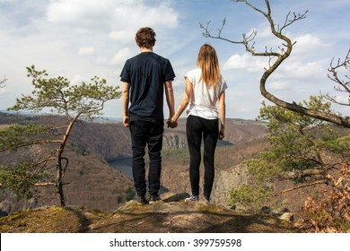 Two young people standing on a rock and holding hands