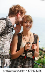 Two young people tourists hiking outdoor. Backpackers couple on summer vacation trip journey. Man whispering to woman ear.