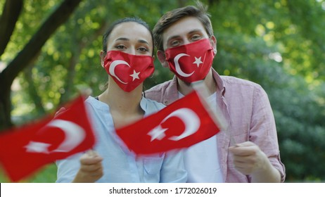 Two young people are waving the Turkish flag while looking at the camera. They wear a medical mask in the form of a Turkish flag to protect them from the virus.